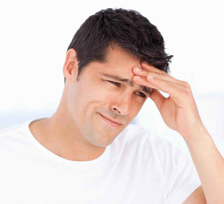 Мужчина в белой футболке держится рукой за лоб