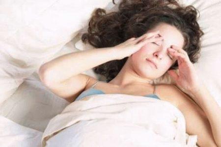 девушка держится пальцами рук за область лба лежа в кровати