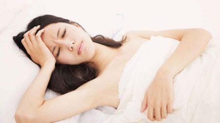 девушка лежит в кровати держась за лоб ладонью