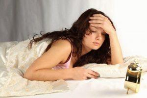 Девушка с закрытыми глазами держится за лоб рукой лежа на кровати