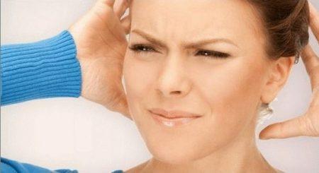 девушка в синей кофте морщится поднеся ладони к голове