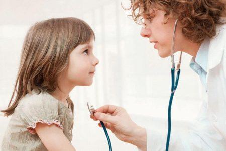 доктор с помощью стетоскопа обследует девочку