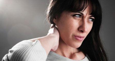 женщина держится ладонью за область шеи