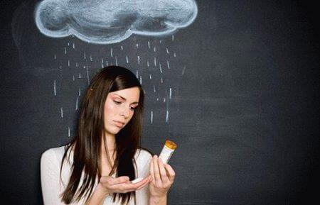 девушка с баночкой для таблеток на фоне графического изображения тучи с дождем