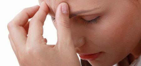 девушка держится двумя пальцами за лоб в области бровей