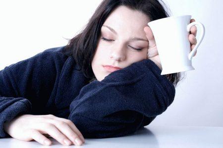 Девушка засыпает с чашкой