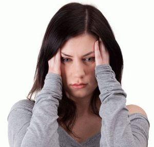 Девушка в серой кофте держится руками за голову