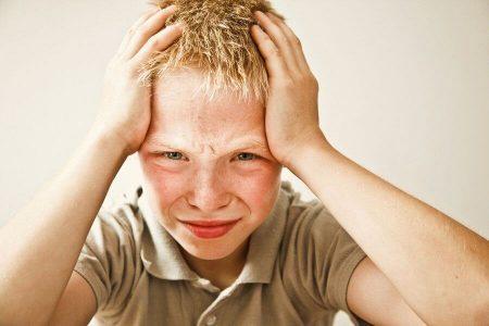 мальчик держится руками за голову