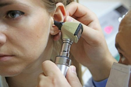 доктор осматривает ухо пациентки