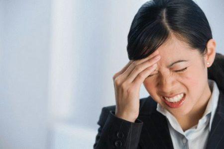 азиатская девушка в костюме держится за лоб