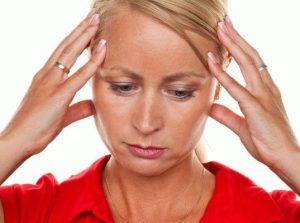 Девушка с грустным лицом держится кончиками пальцев за голову