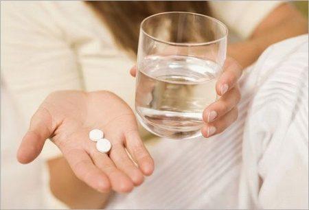 девушка держит в одной руке белые таблетки, а в другой стакан с водой