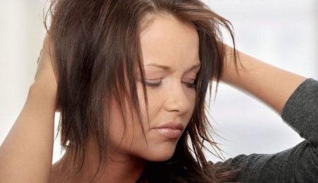девушка обеими руками держится за область затылка
