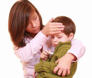 Мама держит ребенка на руках при измерении температуры