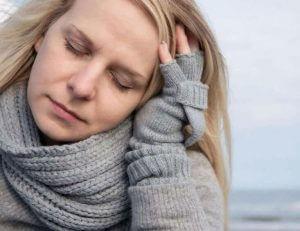 Девушка в серой теплой кофте держится за голову рукой