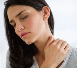 Девушка в серой кофте держится ладонью за шею