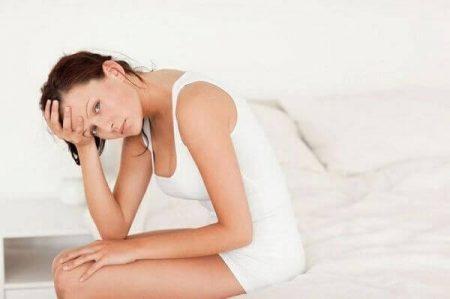 девушка сидит на краю кровати держась за лоб