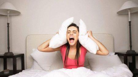 девушка сидит на кровати закрыв уши подушками