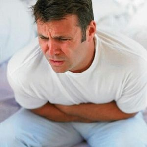 Мужчина сидит согнувшись на кровати держась руками за живот