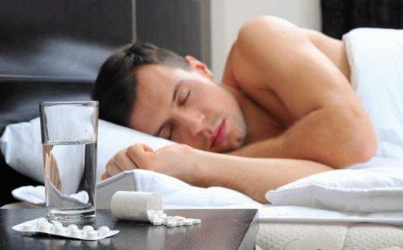 мужчина спит на боку в кровати, на тумбочке стакан с водой и блистэры с таблетками