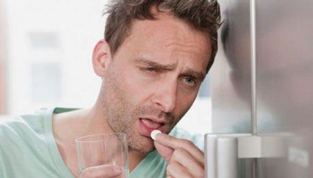мужчина прислонился к холодильнику держа в одной руке таблетку, а в другой стакан с водой