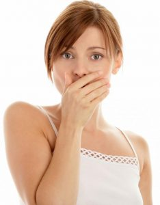 девушка в белой майке прикрыла ладонью рот