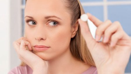 девушка держит в пальцах белую таблетку