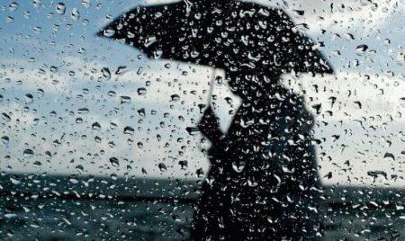силуэт человека под зонтом за окном