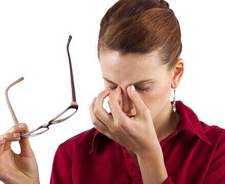 девушка в красной рубашке держит в одной руке очки, а второй держится за переносицу