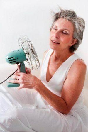 женщина держит в руке вентилятор направив его себе на лицо
